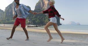 Ζεύγος που τρέχει στην παραλία, άλμα γυναικών στους νέους ευτυχείς τουρίστες ανδρών ερωτευμένους στις διακοπές φιλμ μικρού μήκους