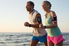 Ζεύγος που τρέχει στην παραλία κατά τη διάρκεια του ηλιοβασιλέματος με τα ακουστικά τους που συνδέονται Στοκ Εικόνες