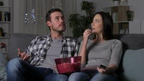 Ζεύγος που υφίσταται μια συσκότιση που προσέχει τη TV απόθεμα βίντεο