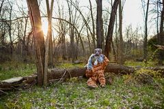 Ζεύγος που φορά τα περίεργα κοστούμια βελούδου που κάθονται από το δέντρο στοκ φωτογραφία