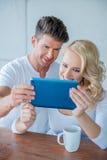 Ζεύγος που χαμογελά δεδομένου ότι διαβάζουν έναν υπολογιστή ταμπλετών Στοκ φωτογραφία με δικαίωμα ελεύθερης χρήσης