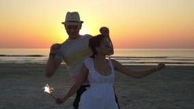 Ζεύγος που χορεύει με ένα κερί πυροτεχνημάτων στην παραλία στην ανατολή απόθεμα βίντεο