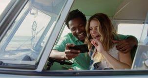 Ζεύγος που χρησιμοποιεί το κινητό τηλέφωνο camper van 4k απόθεμα βίντεο