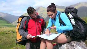 Ζεύγος που χρησιμοποιεί το χάρτη και την πυξίδα για να βρεί τον τρόπο σε έναν βράχο φιλμ μικρού μήκους
