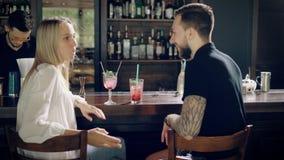 ζεύγος ράβδων Νεαρός άνδρας hipster και συνεδρίαση γυναικών πίσω από το μετρητή φραγμών απόθεμα βίντεο