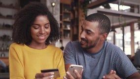 Ζεύγος σε έναν καφέ που ψωνίζει on-line με την πιστωτική κάρτα απόθεμα βίντεο
