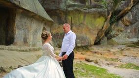 Ζεύγος σε ένα υπόβαθρο των όμορφων βράχων Ζεύγος που στέκεται κάτω από το βουνό απόθεμα βίντεο