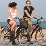 Ζεύγος σε μια παραλία πόλεων με τα ποδήλατα Στοκ Φωτογραφίες