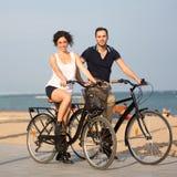 Ζεύγος σε μια παραλία πόλεων με τα ποδήλατα Στοκ Φωτογραφία