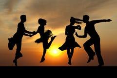 Ζεύγος σκιαγραφιών στον ενεργό χορό αιθουσών χορού στο ηλιοβασίλεμα Στοκ Φωτογραφία