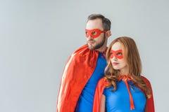 ζεύγος στα κοστούμια superhero που στέκονται μαζί και που κοιτάζουν μακριά στοκ εικόνες με δικαίωμα ελεύθερης χρήσης