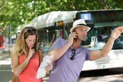 Ζεύγος στα προάστια που κρατούν το χάρτη και που χαιρετούν το λεωφορείο στοκ φωτογραφία