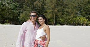 Ζεύγος στην παραλία που αγκαλιάζει τους ερωτευμένους ευτυχείς τουρίστες φιλήματος, νεαρός άνδρας και γυναικών στις καλοκαιρινές δ απόθεμα βίντεο