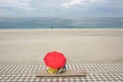 Ζεύγος στην παραλία κάτω από την ομπρέλα Στοκ Φωτογραφίες