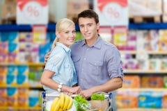 Ζεύγος στην υπεραγορά με το σύνολο κάρρων των τροφίμων στοκ φωτογραφίες με δικαίωμα ελεύθερης χρήσης
