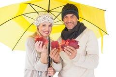 Ζεύγος στη χειμερινή μόδα που παρουσιάζει φύλλα φθινοπώρου κάτω από την ομπρέλα Στοκ εικόνες με δικαίωμα ελεύθερης χρήσης