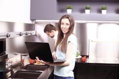 Ζεύγος στον μπροστινό φορητό προσωπικό υπολογιστή στην κουζίνα Στοκ φωτογραφίες με δικαίωμα ελεύθερης χρήσης