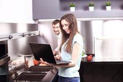 Ζεύγος στον μπροστινό φορητό προσωπικό υπολογιστή στην κουζίνα Στοκ εικόνα με δικαίωμα ελεύθερης χρήσης