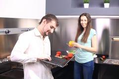 Ζεύγος στον μπροστινό φορητό προσωπικό υπολογιστή στην κουζίνα Στοκ Εικόνες