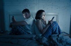 Ζεύγος στο κινητό τηλέφωνο αργά τη νύχτα στα κοινωνικά εσωτερικά προβλήματα εθισμού και σχέσης δικτύων στοκ εικόνες