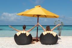 Ζεύγος στο μήνα του μέλιτος που βρίσκεται στις καρέκλες ήλιων στις Μαλδίβες Κρύσταλλο - σαφές μπλε νερό ως υπόβαθρο Όπλα που αυξά στοκ φωτογραφία με δικαίωμα ελεύθερης χρήσης