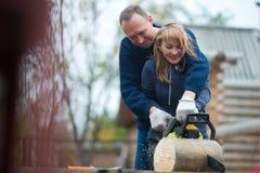 Ζεύγος στο πριονίζοντας ξύλο εγχώριων κήπων φθινοπώρου στοκ φωτογραφία με δικαίωμα ελεύθερης χρήσης