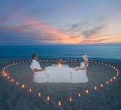 Ζεύγος στο ρομαντικό γεύμα παραλιών με την καρδιά κεριών Στοκ Φωτογραφία