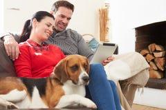 Ζεύγος στο σπίτι με το σκυλί της Pet που εξετάζει την ψηφιακή ταμπλέτα στοκ φωτογραφία με δικαίωμα ελεύθερης χρήσης