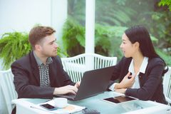 Ζεύγος της νέας επιχείρησης που εργάζεται στο σύγχρονο γραφείο, δύο συνάδελφοι που συζητά το πρόγραμμα διασκέδασης πέρα από ένα l Στοκ Φωτογραφία