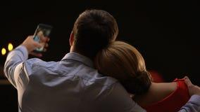 Ζεύγος της Νίκαιας κατά τη ρομαντική ημερομηνία που παίρνει selfie, επέτειος εορτασμού, πίσω άποψη απόθεμα βίντεο