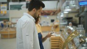 Ζεύγος της Νίκαιας των νέων, του άνδρα και της γυναίκας στην υπεραγορά που επιλέγει τη βιομηχανία ζαχαρωδών προϊόντων απόθεμα βίντεο