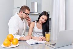 Ζεύγος της πολυάσχολων γυναίκας και του άνδρα το πρωί στην κουζίνα στοκ εικόνα