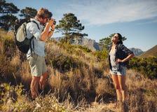 Ζεύγος τουριστών που απολαμβάνει τη φύση και που παίρνει τη φωτογραφία Στοκ εικόνα με δικαίωμα ελεύθερης χρήσης