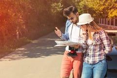 Ζεύγος τουριστών που εξετάζει το χάρτη στο δρόμο Στοκ φωτογραφία με δικαίωμα ελεύθερης χρήσης