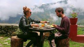 Ζεύγος τουριστών που τρώει το πρόγευμα στα βουνά των Ιμαλαίων απόθεμα βίντεο