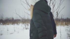 Ζεύγος του περιπάτου εραστών μέσω του βαθιού χιονιού και των κλίσεων στον τομέα απόθεμα βίντεο