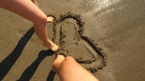 Ζεύγος του χρώματος ανδρών και γυναικών εραστών με τα πόδια τους στην υγρή καρδιά άμμου Η καρδιά πλένεται μακριά από ένα κύμα ζεύ φιλμ μικρού μήκους