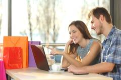 Ζεύγος των αγοραστών που αγοράζουν on-line στοκ εικόνες
