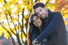 Ζεύγος των εραστών που αγκαλιάζουν στο δέντρο φθινοπώρου Στοκ εικόνα με δικαίωμα ελεύθερης χρήσης
