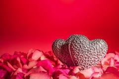 Ζεύγος των διακοσμητικών χαρασμένων καρδιών στα κόκκινα ροδαλά πέταλα Στοκ Φωτογραφία
