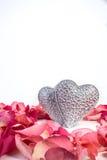 Ζεύγος των διακοσμητικών χαρασμένων καρδιών στα κόκκινα ροδαλά πέταλα Στοκ Φωτογραφίες