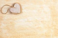 Ζεύγος των καρδιών χαρτονιού που συνδέονται από το σπάγγο όπως το κρεμαστό κόσμημα στο λεκιασμένο φύλλο εγγράφου Στοκ εικόνες με δικαίωμα ελεύθερης χρήσης