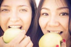 Ζεύγος των κοριτσιών που δαγκώνουν τα πράσινα μήλα Στοκ εικόνες με δικαίωμα ελεύθερης χρήσης