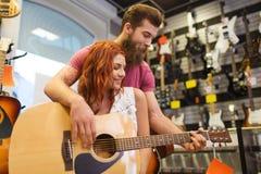 Ζεύγος των μουσικών με την κιθάρα στο κατάστημα μουσικής Στοκ Εικόνες