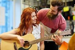 Ζεύγος των μουσικών με την κιθάρα στο κατάστημα μουσικής Στοκ εικόνα με δικαίωμα ελεύθερης χρήσης