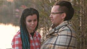 Ζεύγος των νέων: άνδρας και φιλί και αγκάλιασμα γυναικών στο riverbank στο ηλιοβασίλεμα Ρομαντικό βράδυ από κοινού Κορίτσι με φιλμ μικρού μήκους