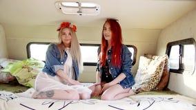 Ζεύγος των νέων γυναικών που κάθονται στον καναπέ στο autotrailer φιλμ μικρού μήκους