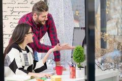 Ζεύγος των νέων σχεδιαστών που εργάζονται στο σύγχρονο γραφείο, δύο συνάδελφοι που συζητά το πρόγραμμα διασκέδασης πέρα από ένα l Στοκ φωτογραφία με δικαίωμα ελεύθερης χρήσης