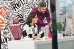 Ζεύγος των νέων σχεδιαστών που εργάζονται στο σύγχρονο γραφείο, δύο συνάδελφοι που συζητά το πρόγραμμα διασκέδασης πέρα από ένα l Στοκ Φωτογραφία
