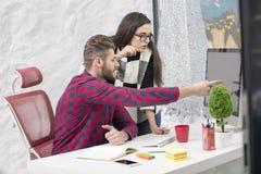 Ζεύγος των νέων σχεδιαστών που εργάζονται στο σύγχρονο γραφείο, δύο συνάδελφοι που συζητά το πρόγραμμα διασκέδασης πέρα από ένα l Στοκ Φωτογραφίες